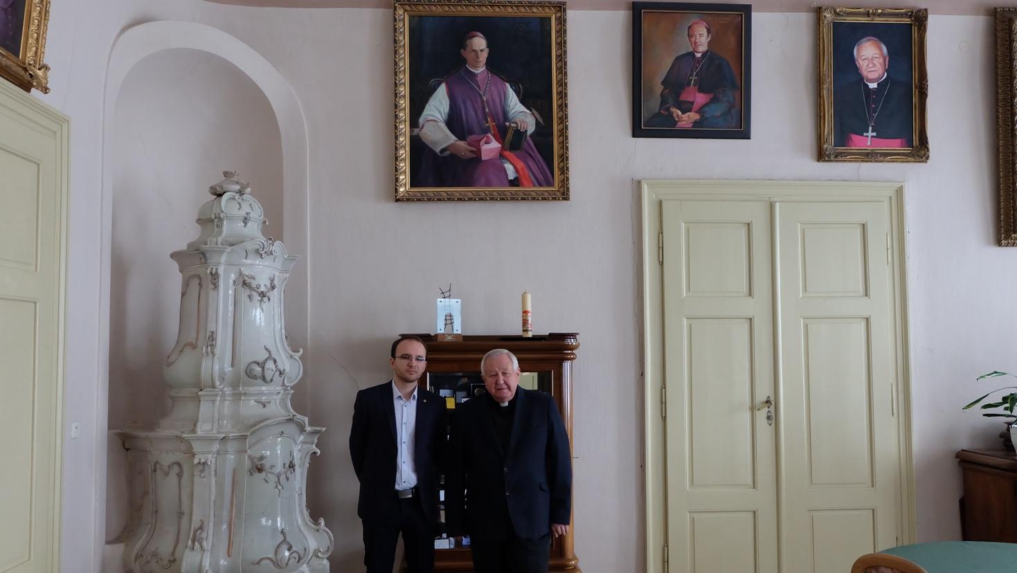 Redaktor Ivo Novák a biskup Štefan Sečka pod portrétmi biskupov (zľava) Jána Vojtaššáka, Františka Tondru a súčasného diecézneho biskupa